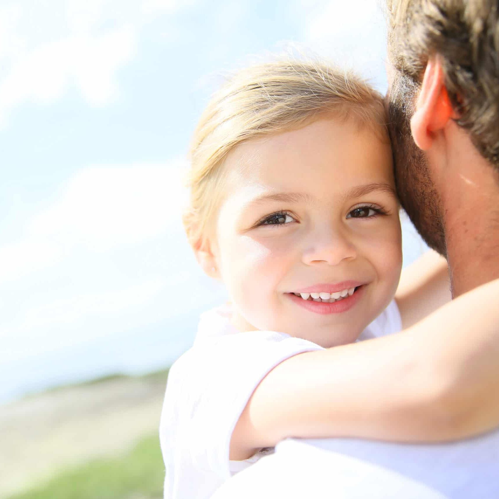 Portrait of cute little girl held in father's arms